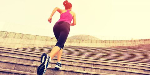 Runner athlete running on escalator stairs. woman fitness joggin